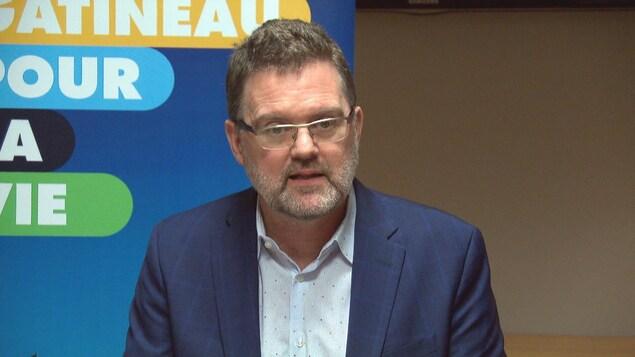 Maxime Pedneaud-Jobin s'adresse aux médias dans un bureau.