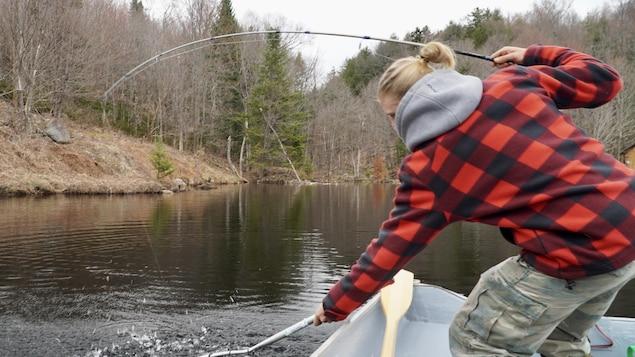 Un homme en chemise à carreau sort avec une puise une truite d'un lac.