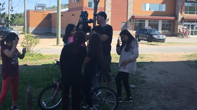 Les enfants de Wemotaci captivés par la caméra de Maxime André, qui leur montre comment elle fonctionne.