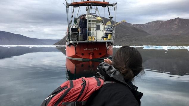 Une femme regarde un voilier au loin.