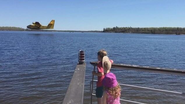 Deux enfants au bout d'un quai regardent un avion se préparant à toucher l'eau d'un lac le 20 mai 2019.