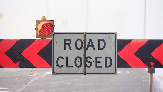 Une barrière routière sur laquelle est apposée une affiche indiquant, en anglais, que la route est fermée à la circulation.