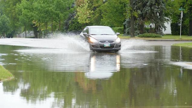 Une voiture traverse une rue inondée dans un quartier résidentiel.