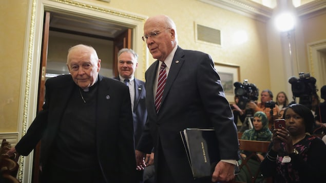 Un vieil homme portant un col ecclésiastique entre dans une pièce avec plusieurs journalistes, à côté d'un autre homme en complet avec une cravate.