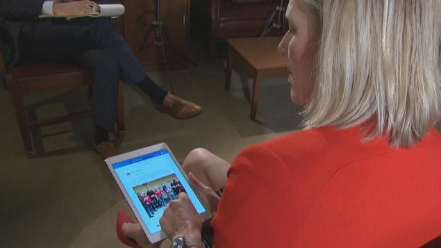 Catherine McKenna lit sur une tablette des messages publiés sur les réseaux sociaux.