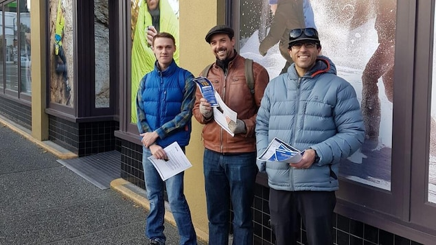 Trois hommes sourient devant un magasin MEC.