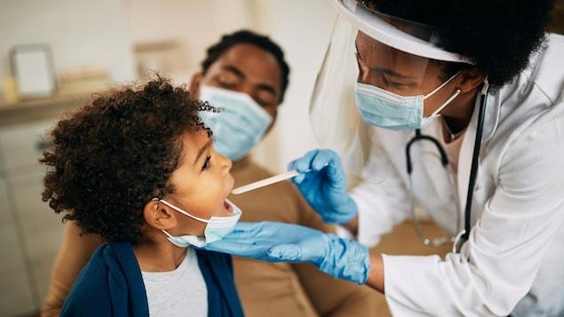Médecin de famille examinant la gorge d'un petit garçon.