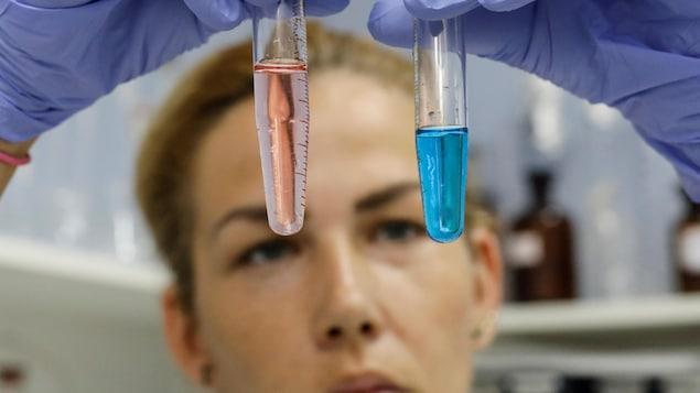 Une professionnelle du domaine médicale examine deux éprouvettes dans un laboratoire.