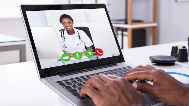 Photo des mains d'un homme sur un clavier d'ordinateur. Le patient parle avec son médecin à l'écran.
