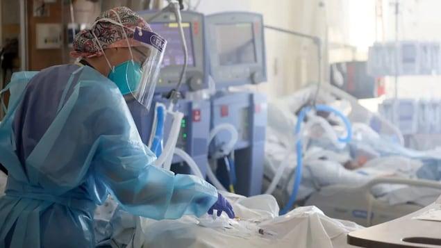 Une infirmière s'occupe d'un patient dans une salle des soins intensifs.
