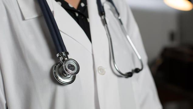Haut de corps d'un médecin portant un stéthoscope autour du cou.