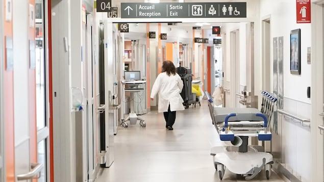 Une femme vêtue d'un sarrau blanc marche dans un corridor d'hôpital où l'on voit une civière.