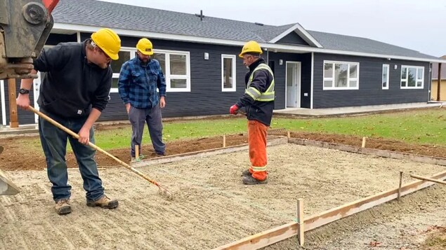 Trois travailleurs de la construction préparent une entrée de ciment.