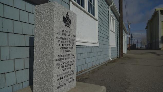 Un panneau devant un bâtiment en bois indique que des prisonniers de guerre allemands ont été détenus sur ce site du janvier 1942 à mai 1945.