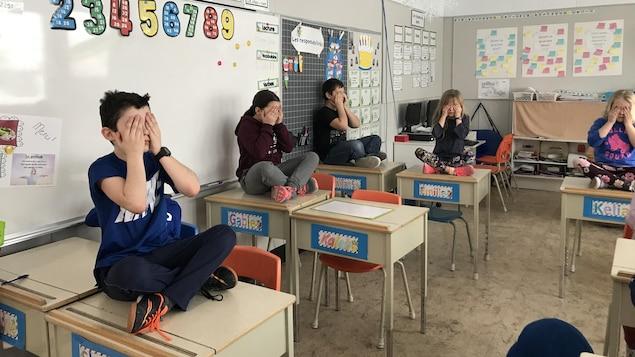 Des enfants sont assis sur leur pupitre, les mains sur les yeux, méditant.