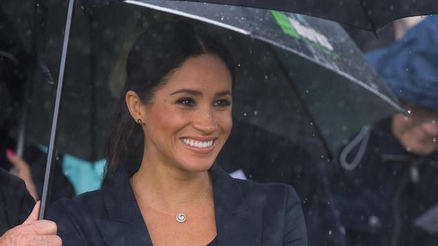 Meghan Markle se tient sous un parapluie.