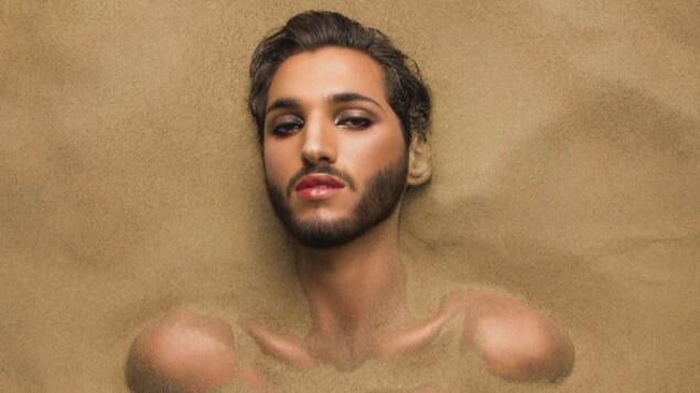 Un homme portant une courte barbe et du rouge à lèvres est enterré jusqu'au cou dans du sable fin.