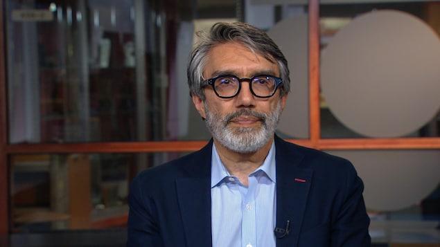 Mehran Ebrahimi, spécialiste de l'aviation, portant des lunettes et une petite barbe. Il regarde la caméra alors qu'il est interviewé dans nos studios de Montréal.