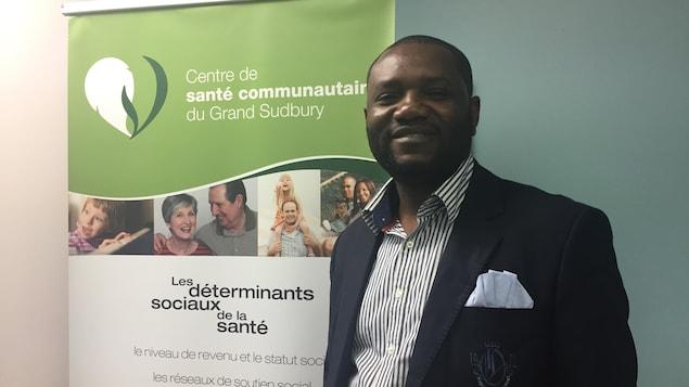 Mekila Kambo devant une banderole verte du Centre de santé communautaire du Grand Sudbury.