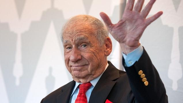 L'acteur vêtu d'un complet et d'une cravate rouge envoie la main alors qu'il prend la pose pour les caméras sur un tapis rouge.