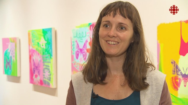 Une dame souriante devant des oeuvres d'art.