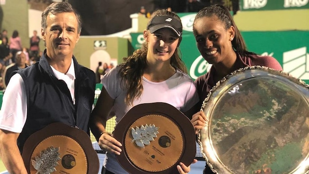 Un homme et deux jeunes femmes tiennent des trophées ronds