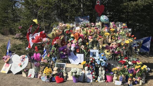 Un imposant mémorial rempli de fleurs, de ballons, de drapeaux et de messages de condoléances installés au bord d'une route.