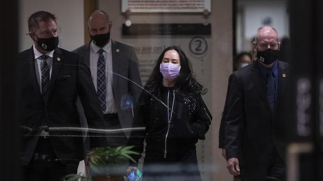 La directrice financière de Huawei marchant aux côtés de trois hommes.