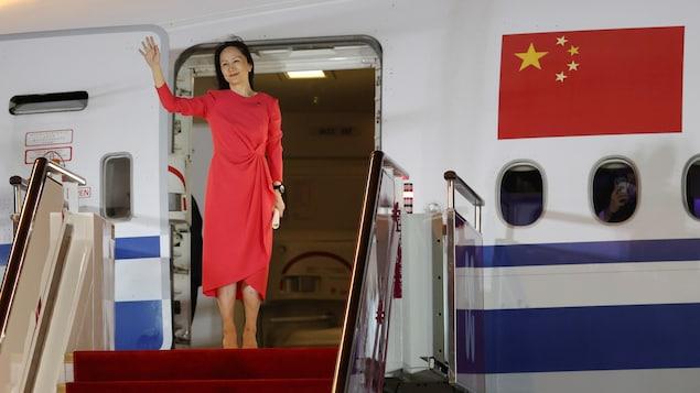 Meng Wanzhou salue la foule à la sortie de son avion.