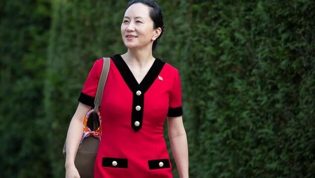 Meng Wanzhou souriante et portant une robe rouge devant un mur de cèdres.