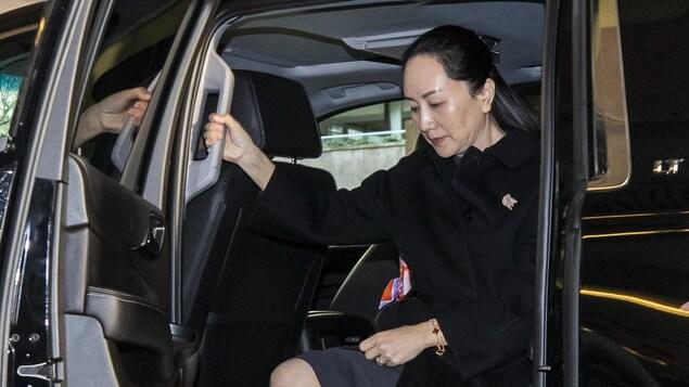 Une femme sort d'une voiture.