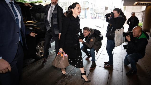 La directrice financière de Huawei marche en direction de la porte d'entrée de la Cour suprême de la Colombie-Britannique et des photographes et caméramans témoignent de son passage.