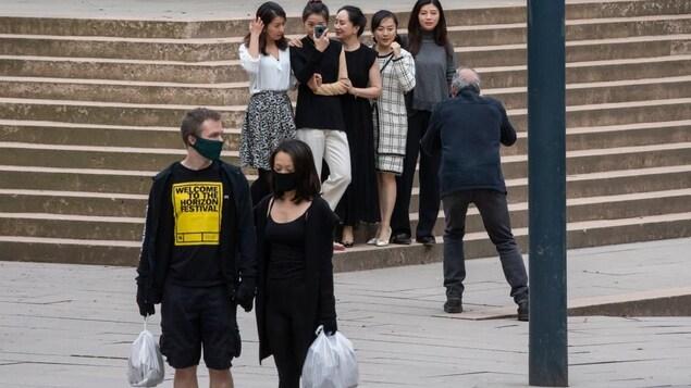 Un groupe de femmes, dont Meng Wanshou, se fait photographier sur des marches. Devant, un couple portant des masques marche.