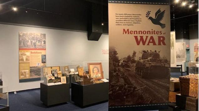 Une salle de musée du  Mennonite Heritage Village où on voit des présentoirs et un panneau d'interprétation sur lequel il est écrit  « Mennonites war » en rouge.