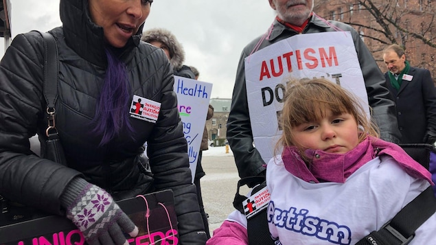 Une mère et une petite fille tiennent des pancartes de protestation.