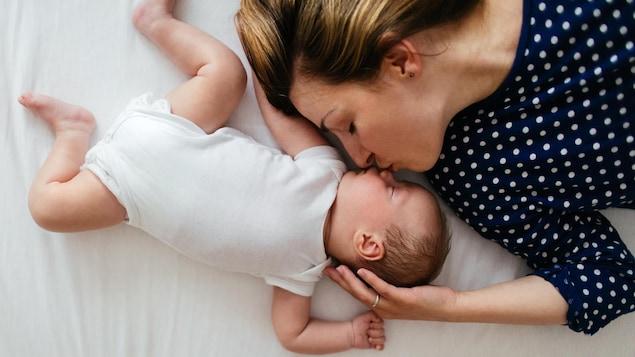 Une photo d'une mère en train d'embrasser son bébé endormi sur un grand lit.