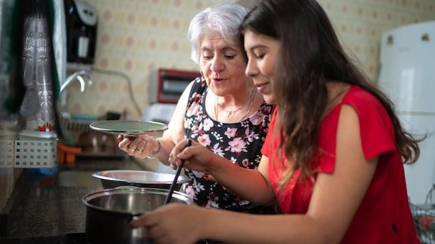 Deux femmes, dont une plus âgée, sont en train de cuisiner et regardent le contenu d'une marmite.