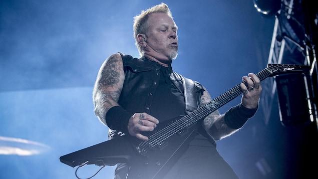 L'homme joue de la guitare sur scène lors d'un concert.