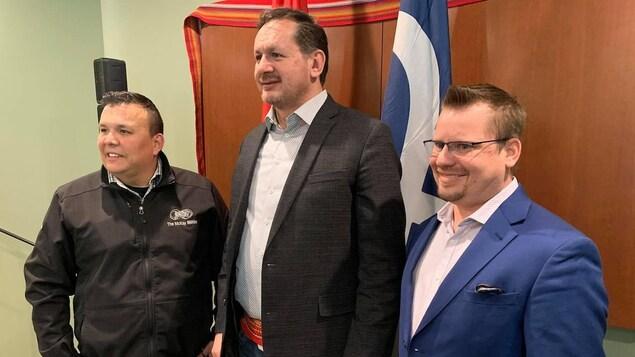 Trois leaders métis se tiennent côte à côte.