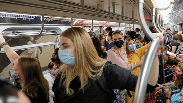 Des usagers d'un métro portent des masques.