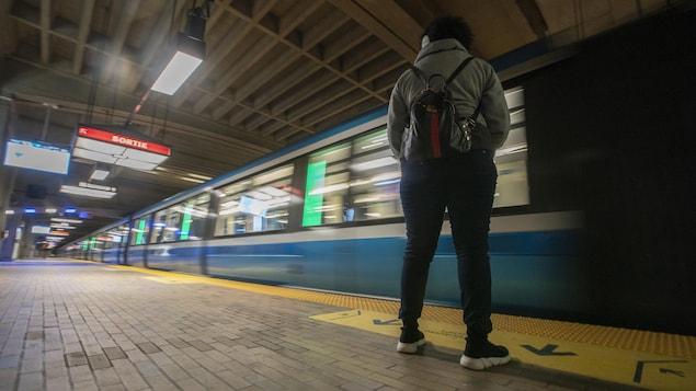 Une personne attend le métro.