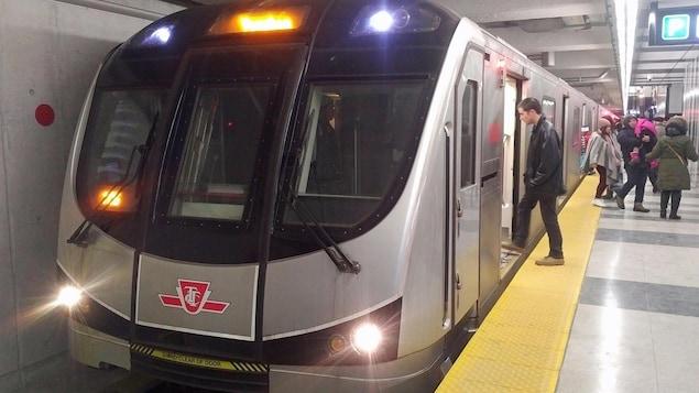 Des usagers montent à bord d'une rame de métro.
