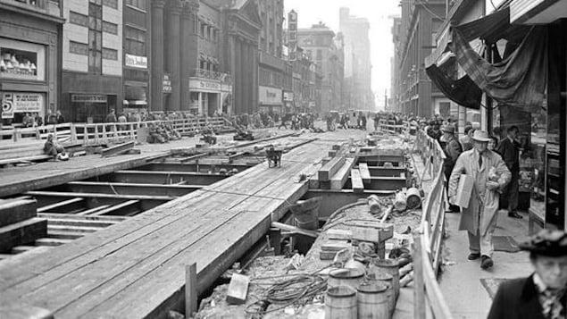 Grande tranchée sur la rue avec les planches de bois qui la recouvre. Les passants sont sur les trottoirs étroits.