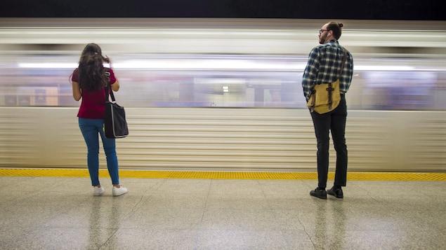Un jeune homme et une jeune femme attendent le métro sur la plateforme.