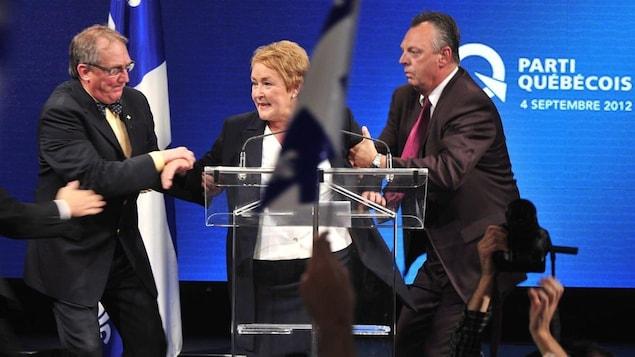 Des gardes du corps de la Sûreté du Québec escortent Pauline Marois d'urgence au milieu de son discours, le soir du 4 septembre 2012.