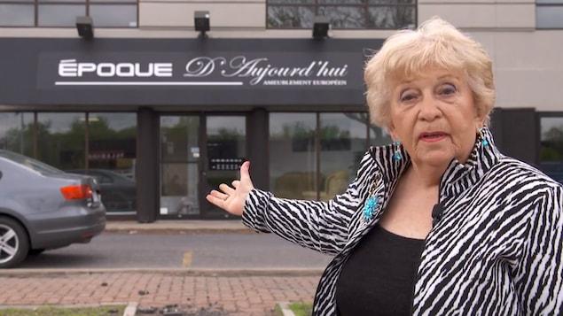 Nicole Bourassa montre de la main l'entrée d'un commerce.