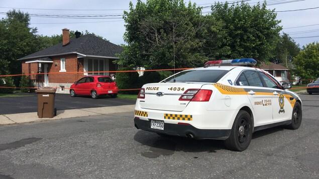 Une voiture de police devant une scène de crime