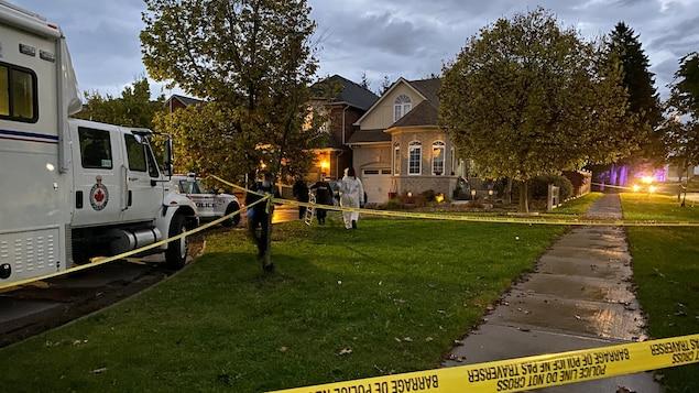 Des enquêteurs de la police devant une scène de crime à Whitby en Ontario.
