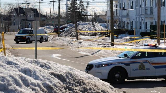 Des véhicules de police encerclent la scène de crime.