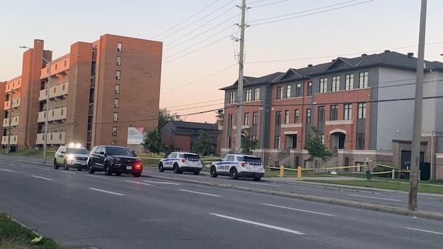 Des voitures de police devant un immeuble.